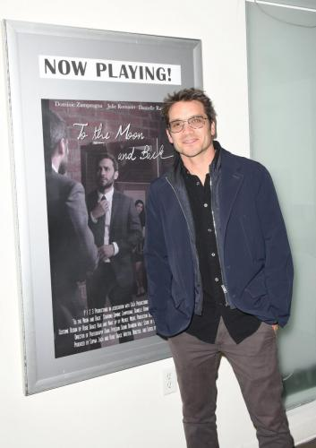 Dominic Zamprogna in front of the movie poster for the film.